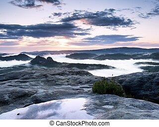 View over wet sandstone rocky peak into forest valley, daybreak Sun