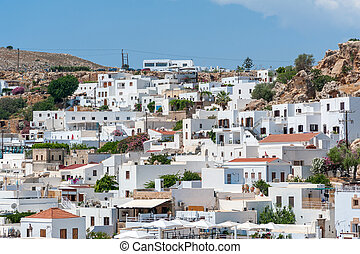 View over whitewash houses with rooftops in Lindos Town from path leading to Acropolis. Greek Island of Rhodes. Europe.