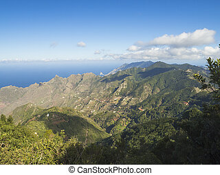 view point Amogoje, green hills with rock in the sea El Draguillo in anaga mountain, tenerife canary island spain with dramatic blue sky white clouds background