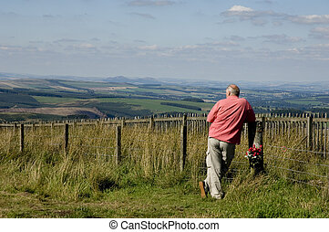 Middle aged man standing in England looking into Scotland