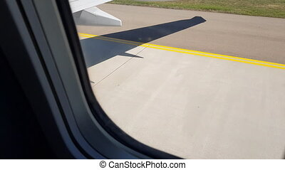 View through a passenger airplane window plane taxiing from runway to terminal after landing