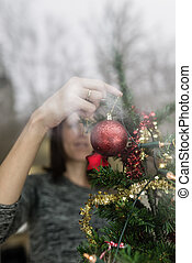 View through a window of a woman hanging red bauble on a tree