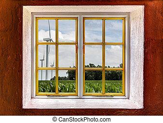 View through a window of three wind turbines