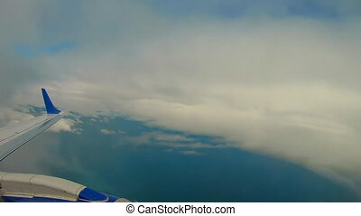 View through an airplane window. Flying over the Mediterranean Sea through cirrus and cumulus clouds and little turbulence, showing