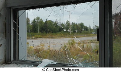 View through broken window. Traffic passing on the road....