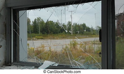 View through broken window. Traffic passing on the road. Two...