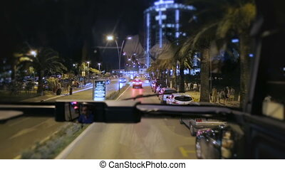 View through bus windshield which ride on the night road street in tourist resort town