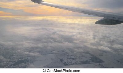 View through dirty window of airplane at part of the wing and sunset cloudy sky