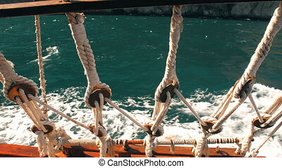 View through ship ropes at sea - view from the stern of the...