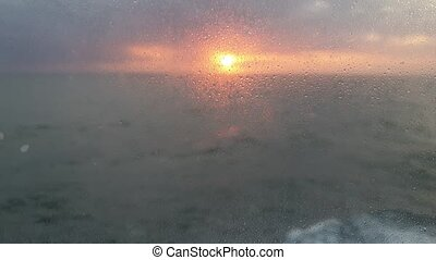 View through the cabin window on ocean with sunset.