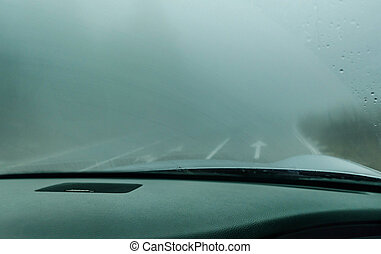 View through the cars windshield  in the winter fog on the road