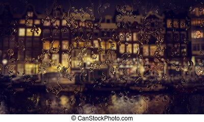 View through the glass with raindrops traditional houses