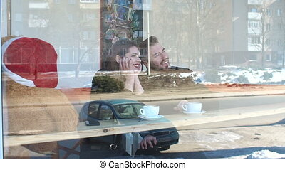 View through the window of a young couple in a coffee shop.