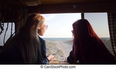 view through the window of an autotrailer at sea between two women with flowing hair fluttering in the wind in the rays of the sun