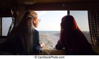 view through the window of an autotrailer at sea between two young women with flowing hair fluttering in the wind in the rays of the sun
