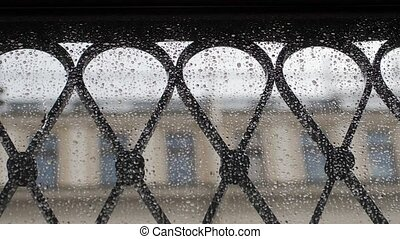 View through the window with drops changes focus to people walk in the rain. Slow motion,