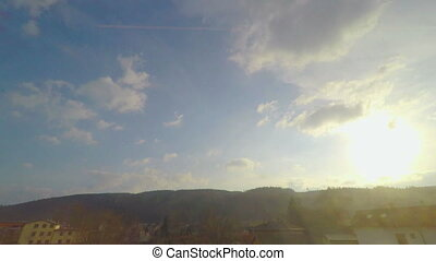 """View through train window, sunny blue sky with clouds, trees, hills on horizon"""