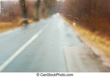 view through wet glass, rainy weather, wet road, rain drops on the car