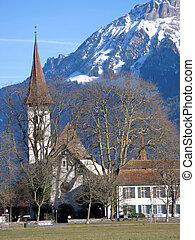 View to an old church and mountains in Interlaken, Switzerland