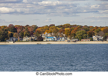 view to coast of New London on a sunny day with old traditional wooden houses at the beach