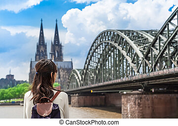 View to Cologne - Young woman seen from back looking to...