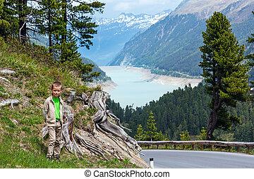 Summer view to Gepatsch-Stausee lake from alpine road and small boy near (Kaunertal, Austria, Tirol).