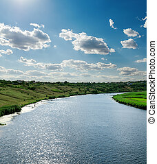view to river with reflection under blue cloudy sky and sun