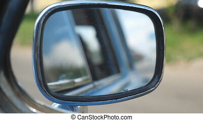View to side mirror of old retro car with blurred city at background. Vintage automobile driving at the city street on sunny summer day. POV Close up Slow motion