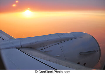 View to sunset sky and sun from the plane with the detail of...