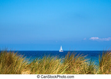 View to the Baltic Sea with sailboat in Warnemuende, Germany.