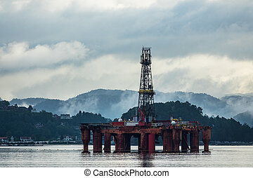 View to the Lyngdalsfjord with drilling rig in Norway