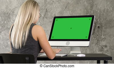 Businesswoman sitting at her desk in the office working on a desktop monitor. Green Screen Mock-up Display.