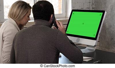 Young couple looking at monitor talking. Man makes a call....