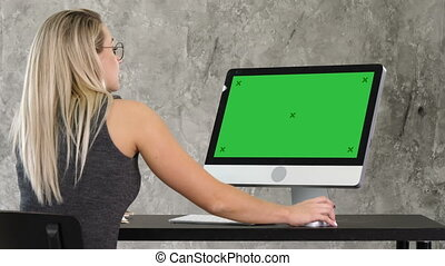 Young friendly operator woman talking and working on the computer. Green Screen Mock-up Display.