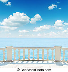 view to the sea from a balcony under cloudy sky