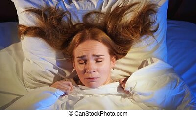 View top. A woman with red hair sleeps in bed and sees a nightmare, her face winces and grimaces. problem of poor sleep.