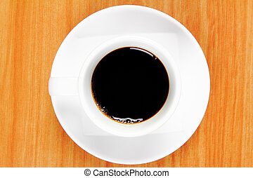 View top of black coffee cup on wood