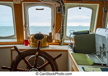 View trough capitan cabin with steering wheel on the boat