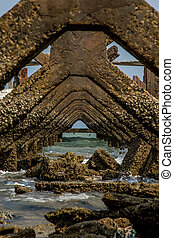 View under at Broken old structure remains of pier in the sea.