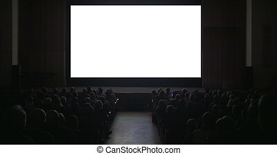 Viewers in dark cinema hall with blank screen