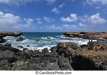 A scenic look on Aruba's black sand beach with rugged lava rocks.