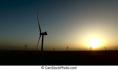 Views of large wind turbines in the steppe at sunset. Silhouette. Aerial survey
