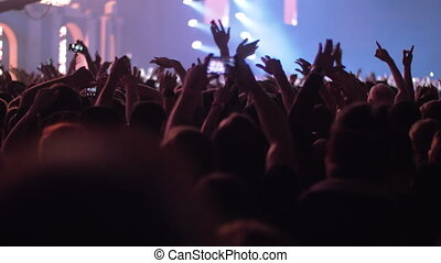 Vigorous audience dancing with hands up at the concert