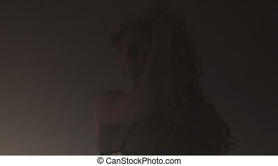 Vigorous curly blonde dancing in a smoke in the flashing...