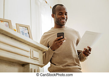 Vigorous smiling man holding a phone
