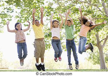 vijf, jonge, vrienden, springt, buitenshuis, het glimlachen