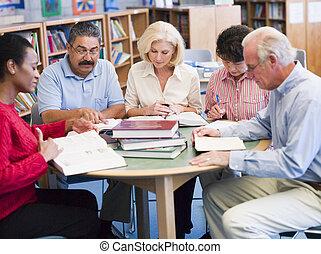vijf mensen, zittende , in, bibliotheek, met, boekjes , en, notepads, (selective, focus)