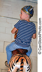 viking boy on the toy tiger looking aside