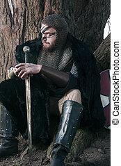 Viking in fur sitting near the tree