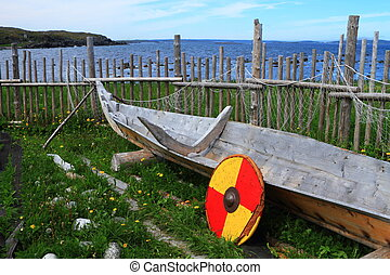 Old boat and old Viking shield at the Viking settlers in L'Anse aux Meadows national historic site on the island of Newfoundland, Canada